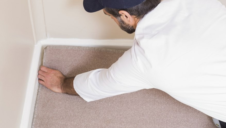 A man installs carpeting near a wall corner.