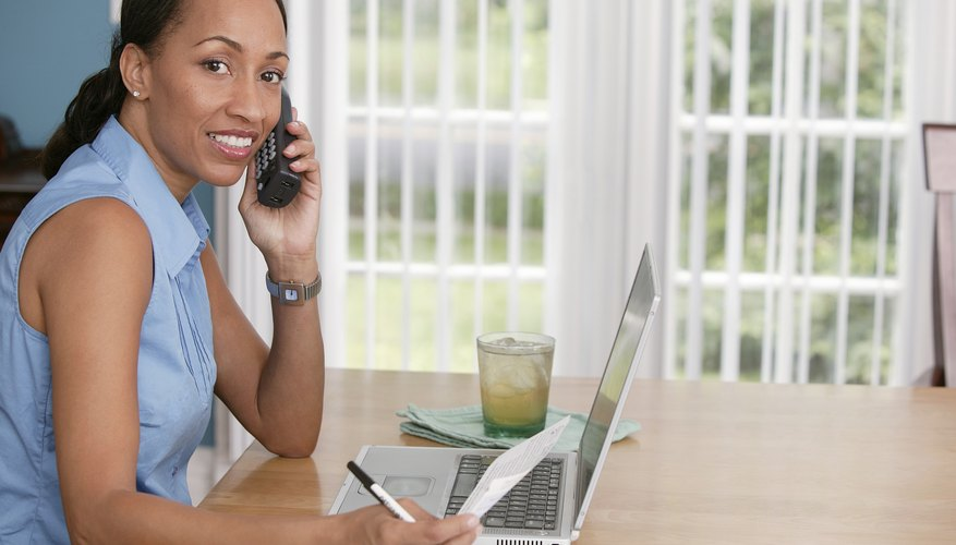 Woman talking on phone while using laptop computer.
