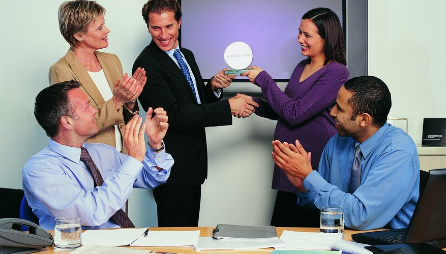 Businessman Being Given an Award for Achievement With His Colleagues Applauding Him