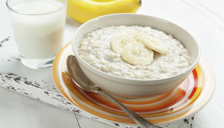 A bowl of oatmeal with sliced bananas.