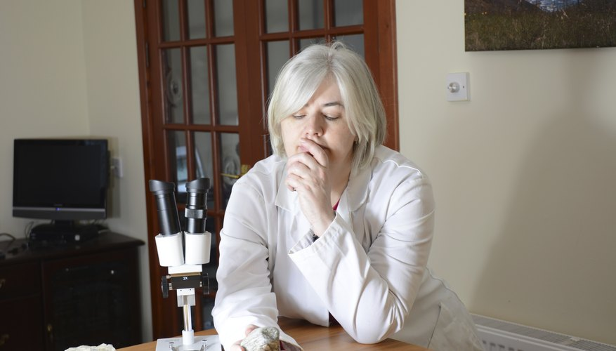A scientist examining rocks with a microscope.