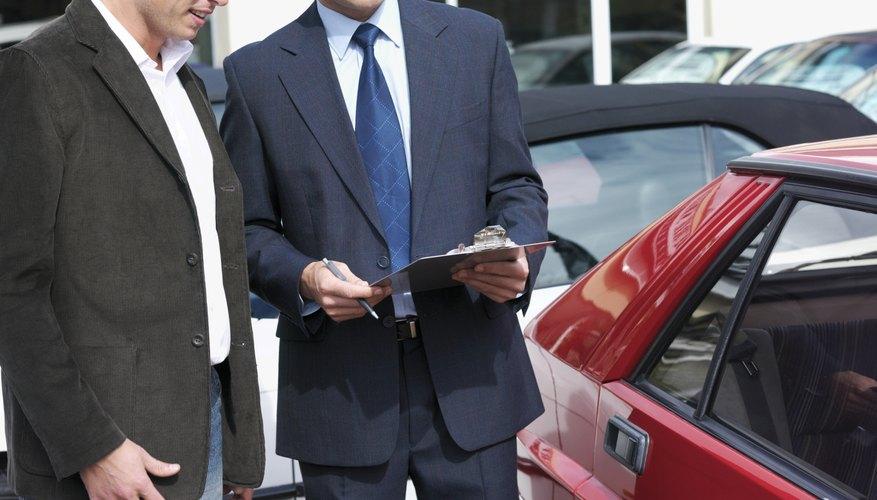 Car salesman talking with customer outdoors