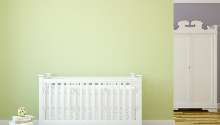 A green accent wall juxtaposed next to a baby's crib