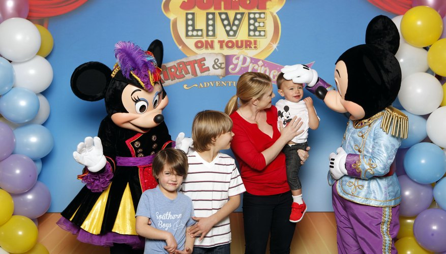 Mickey and Minnie mouse posing with a family.