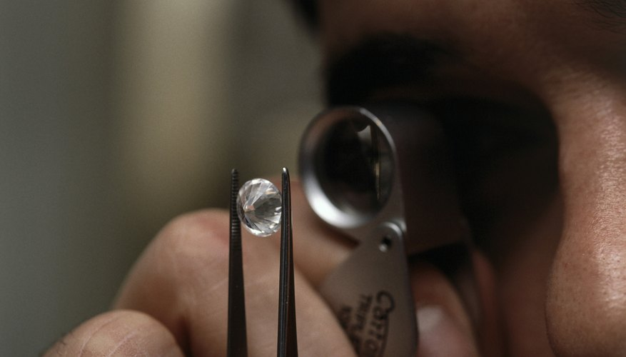 Man looking at diamonds through magnifying glass