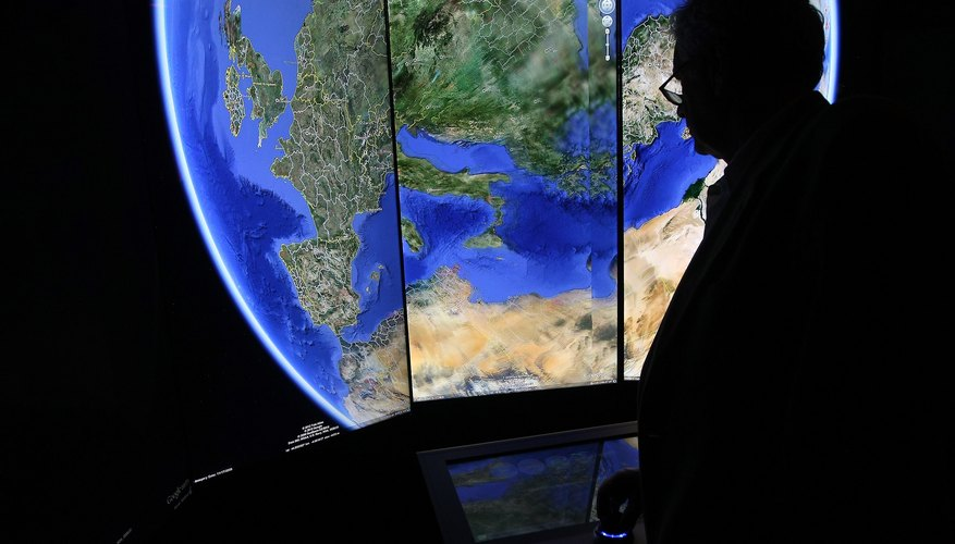 Man looking at three-dimensional rendering of planet Earth