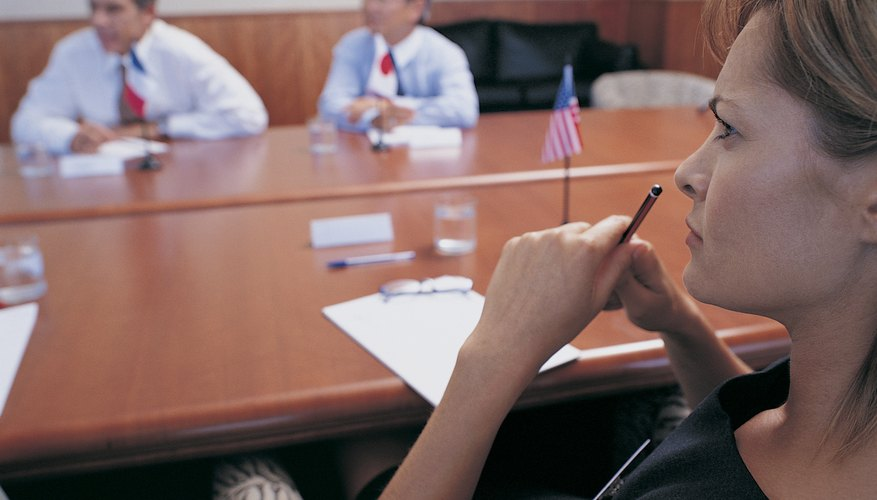 Businesswoman Holding a Pencil and Listening at a Meeting Around a Boardroom Table