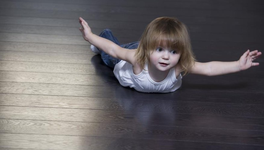 A little girl lying on a hardwood floor