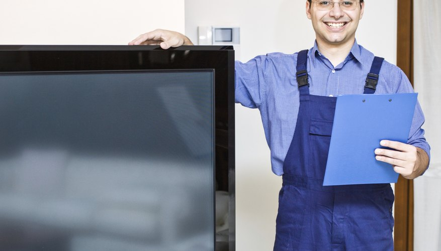 A smiling TV maintenance man stands next to a television.