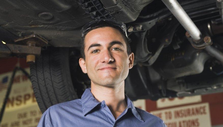 Smiling mechanic underneath car