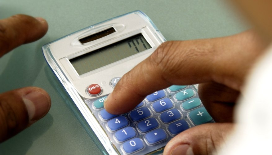 Close-up of man using calculator