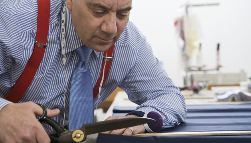 A tailor cuts fabric with a pair of scissors