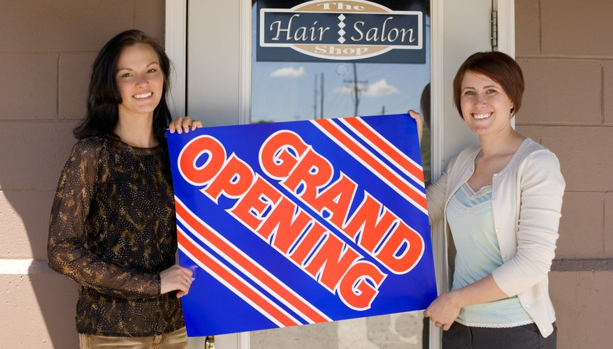 Women holding Grand Opening sign