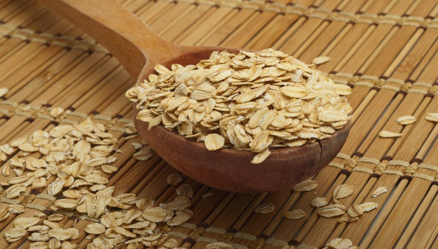 A wooden spoonful of dry oats.