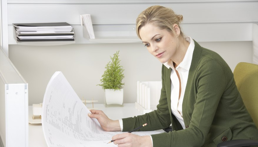 Young businesswoman looking at paperwork at desk