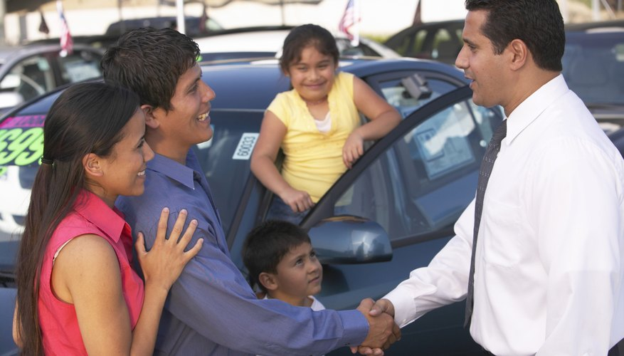 A husband and wife shake hands with a car dealer