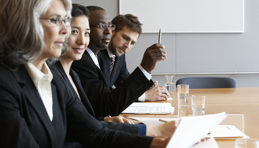 Executives in conference room reading documents, side view