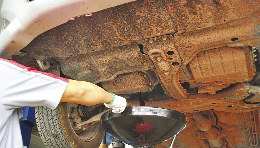 A mechanic changes a cars oil.