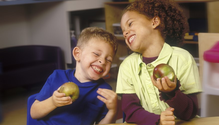 Children Eating Apples And Laughing In Classroom