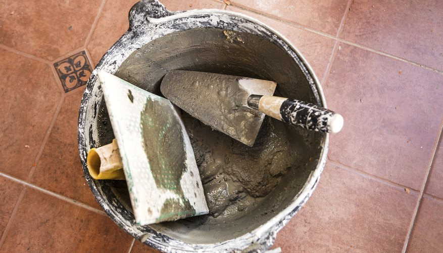Close-up of a spatula and other tools in a bucket of cement