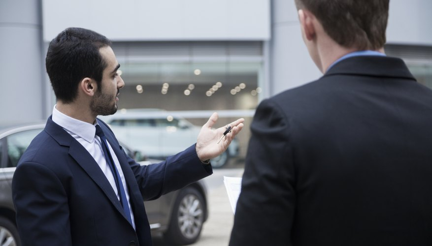 Car salesman holding the keys to a new car