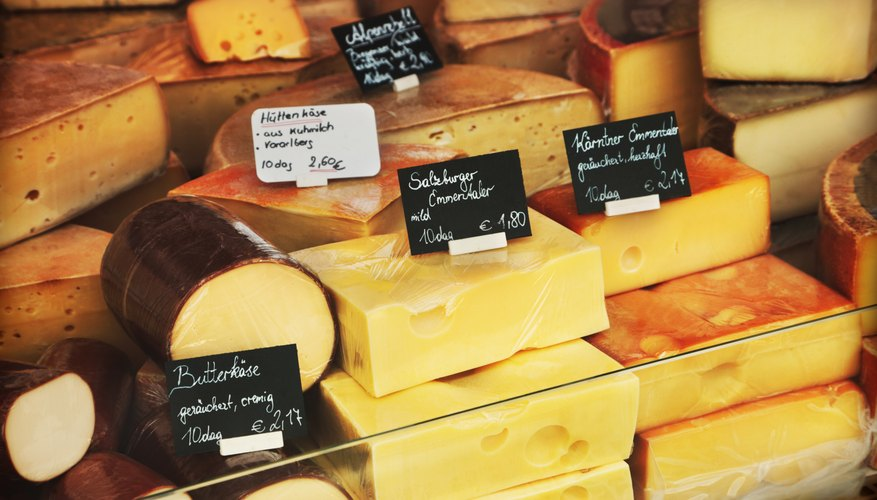 An assortment of cheeses at a deli counter