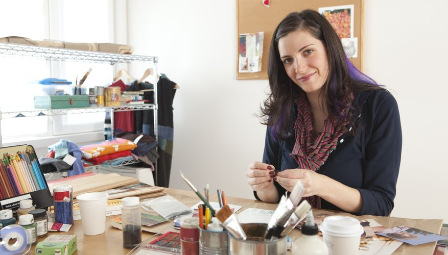 Attractive young woman working on craft project at desk