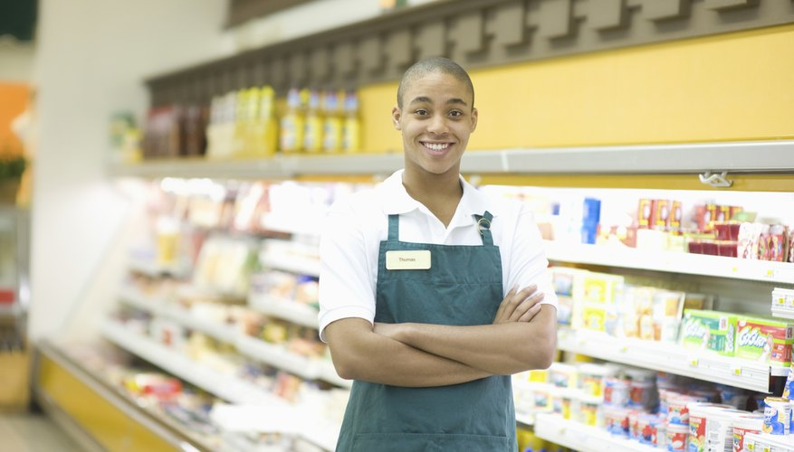 Young grocery store employee wearing apron.