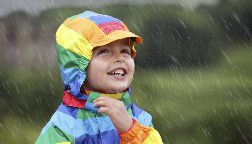 Young child in raincoat smiling as rain falls