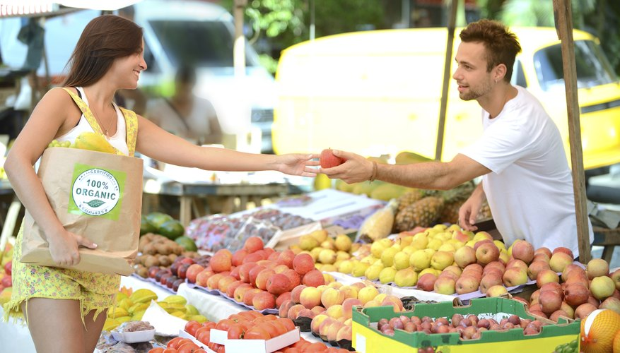 Greengrocer handing out a fruit to a consumer.