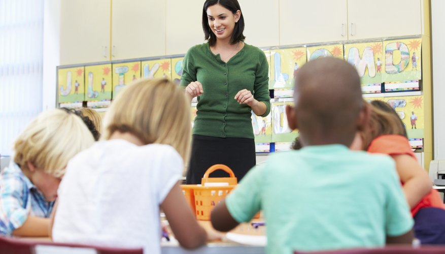 Teacher Talking To Elementary Pupils In Classroom