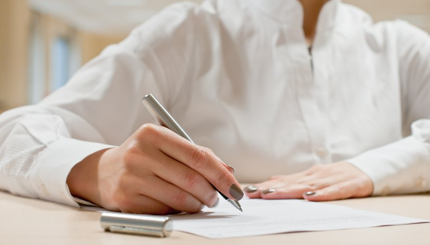 A woman is signing a contract.