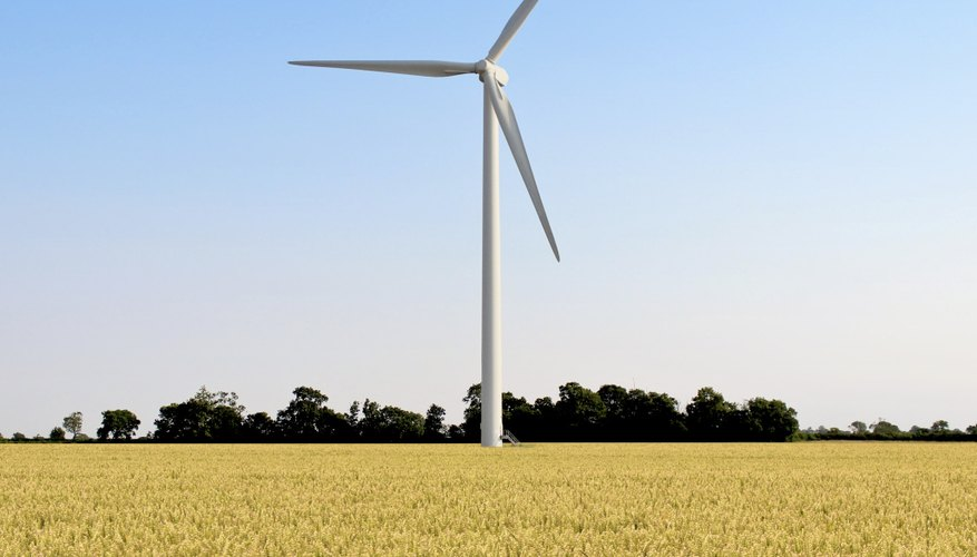 A wind turbine spins in the middle of a wheat field.