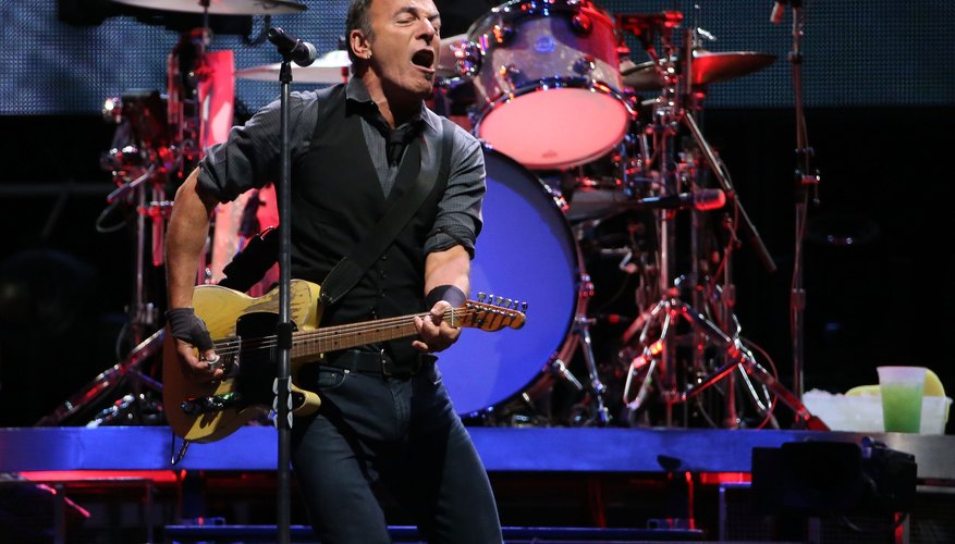 Bruce Springsteen singing into the mic while playing the guitar on stage.
