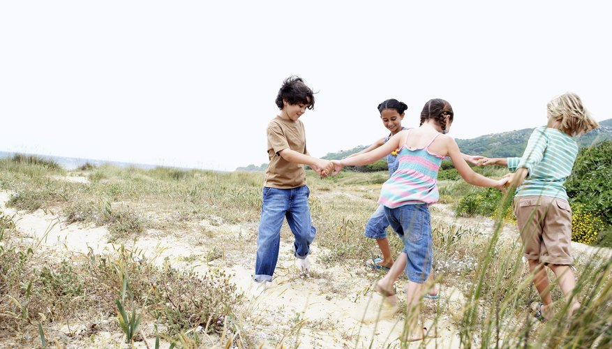 Children holding hands while playing in field.
