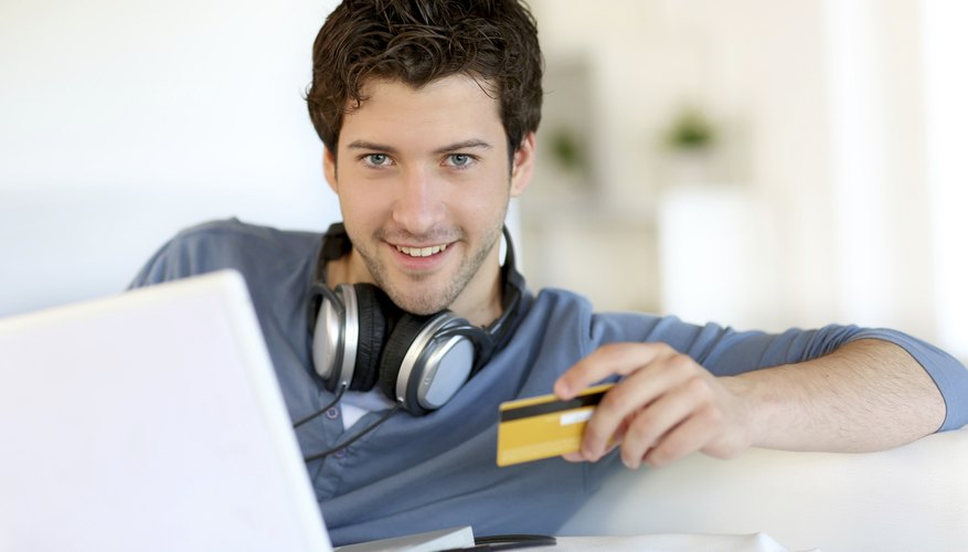 Image of a man holding a debit card.