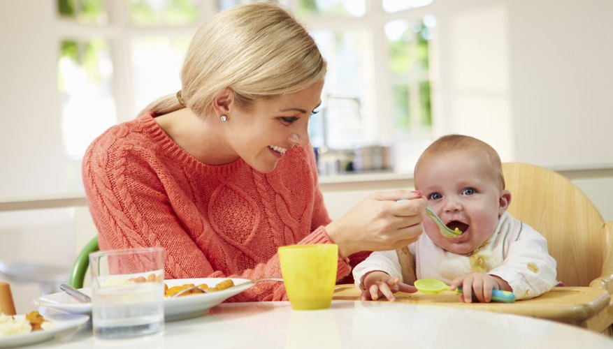 Mother spoon feeding her baby.
