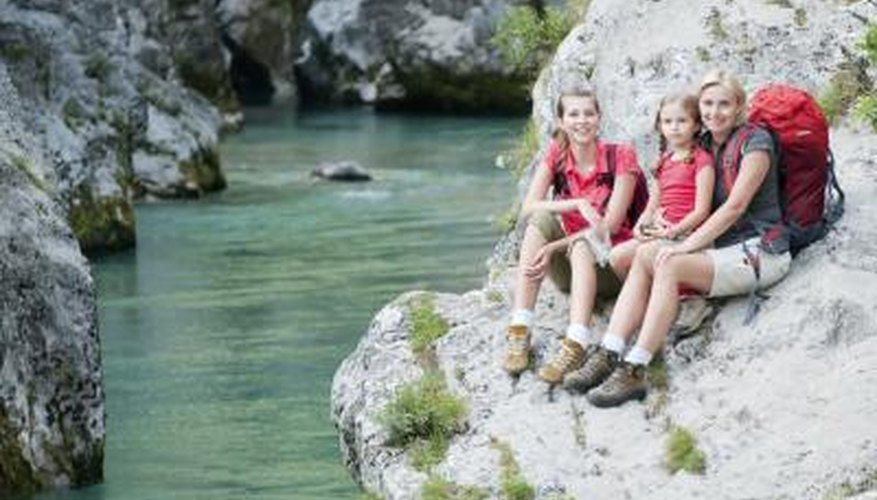 A mother and two daughters sit on a large rock next to a stream.