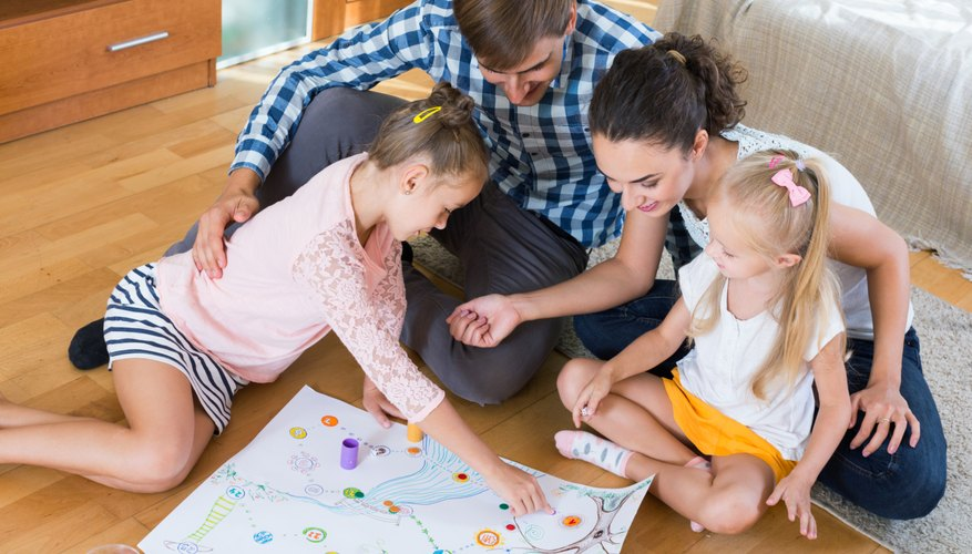 A family plays a board game on the floor in the lounge room.