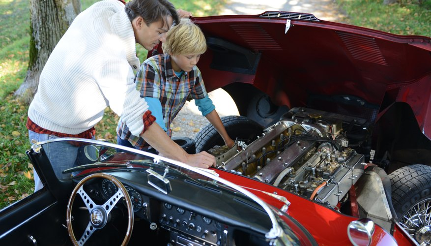 Father and son looking at classic car engine