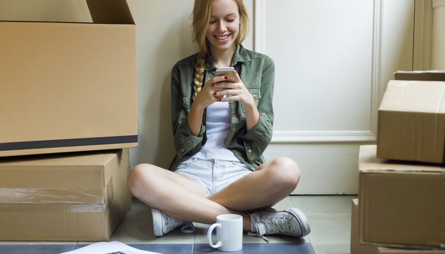 A woman sitting next to cardboard boxes while using her smartphone