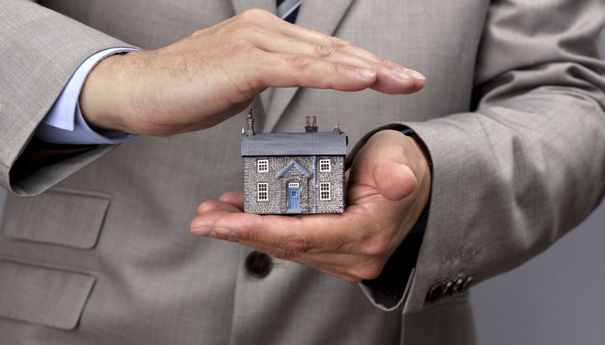 Insurance agent with a model house.