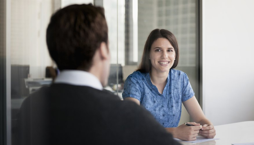 A manager and employee talking in an office.