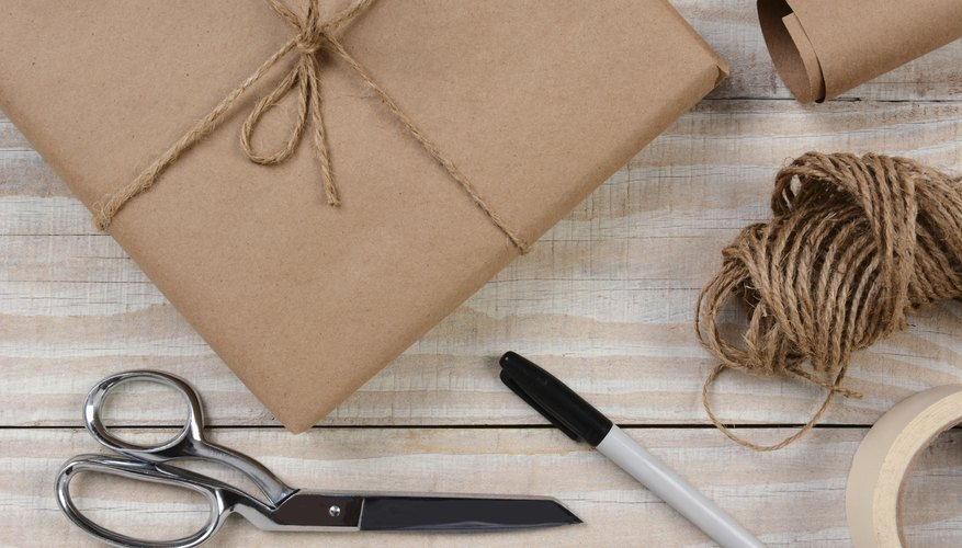 A gift wrapped in brown butcher paper sitting on a table with scissors, tape, string and a marker.