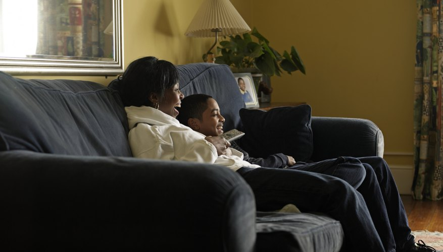 Mother and son (12-13) watching tv together sitting on sofa
