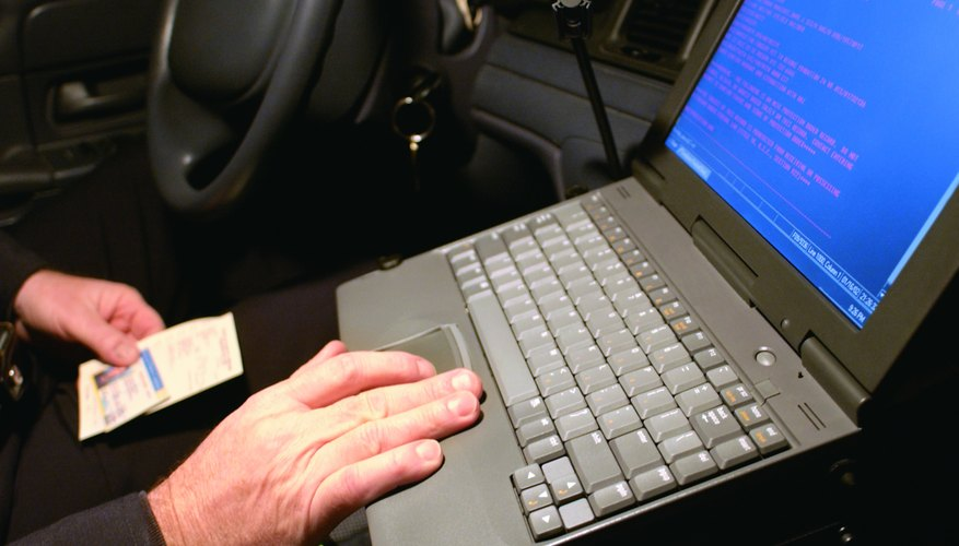 Photo, police officer entering information into a laptop computer in police car, Color, High res