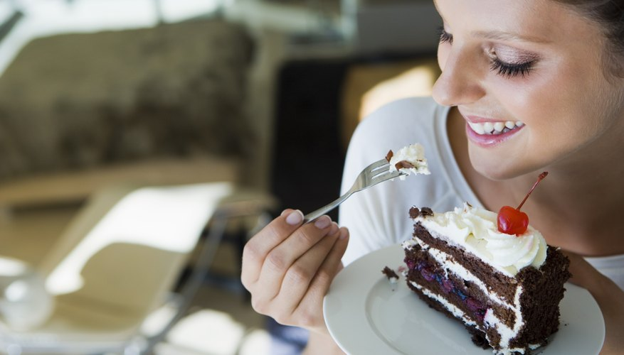 A woman is eating a large slice of chocolate cake.
