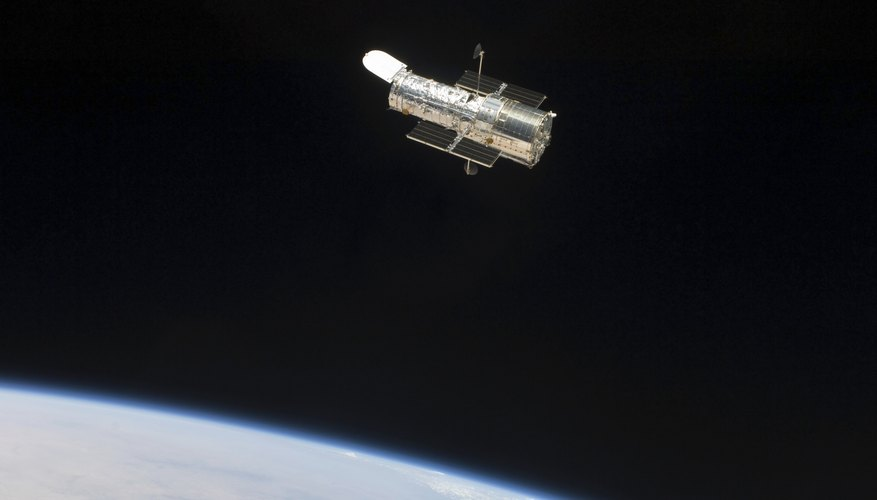 The Hubble Space Telescope floats in space through Earth's exosphere.