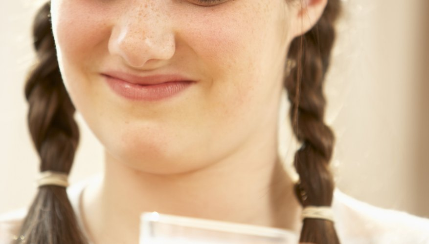 Girl frowning at glass of milk