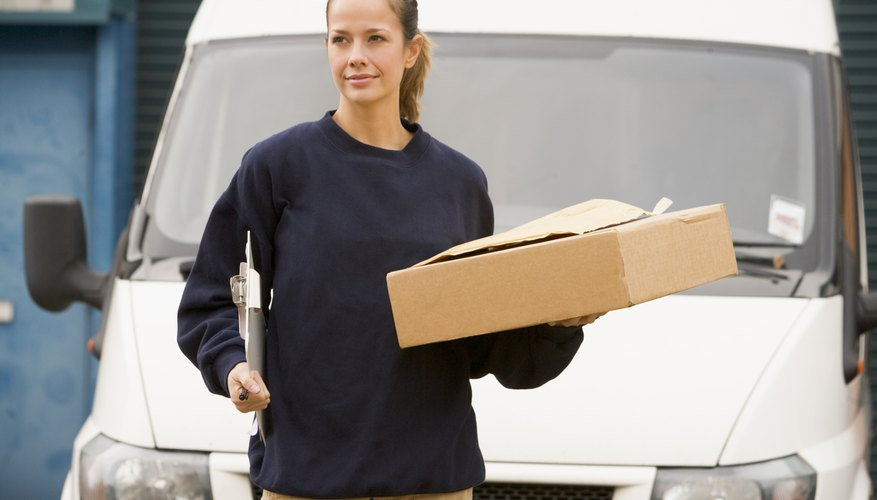 Deliveryperson standing with van with clipboard and box